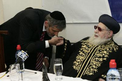 Shas leader kisses Rabbi Yosef's ring.